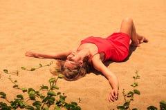 blondes Mädchen der oberen Ansicht im roten Kittel liegt auf Sand mit den Händen beiseite Stockbilder