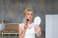 Blondes Mädchen der schönen Braut im Hochzeitskleid mit Frisur und hellem Make-up auf dem Haupthintergrund, der im Spiegel schaut Stockfotografie