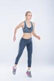 Blondes Mädchen der schönen Eignung in der Sportkleidung läuft auf grauem Hintergrund Stockbilder