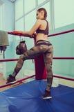 Blondes Mädchen der sexy Eignung in der Sportabnutzung mit perfektem Körper in der Verpackenturnhalle, werfend im Boxring auf Spo Stockfotografie