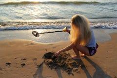 Blondes Mädchen in der Sonnenbrille mit Metalldetektor Stockfotos