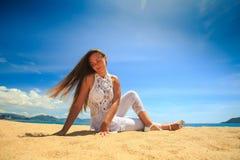 blondes Mädchen in der Spitze im Yoga asana Beinkreuz auf Strand Lizenzfreies Stockfoto