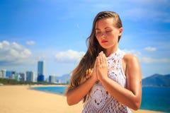 blondes Mädchen in der Spitze sitzt in Yoga asana Blitz auf Strand Stockfotografie
