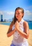 blondes Mädchen in der Spitze sitzt in Yoga asana Blitz auf Strand Lizenzfreies Stockbild