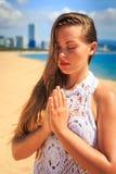 blondes Mädchen in der Spitze sitzt in Yoga asana Blitz auf Strand Stockbilder