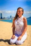 blondes Mädchen in der Spitze sitzt in Yoga asana Blitz auf Strand Lizenzfreie Stockbilder