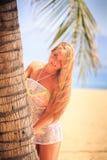blondes Mädchen in der Spitzenahaufnahme lehnt sich aus Palmenlächeln heraus auf Strand Stockbilder