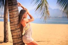 blondes Mädchen in der Spitzenahaufnahme lehnt sich mit Rückseite auf Palme auf Strand Lizenzfreie Stockbilder