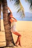 blondes Mädchen in der Spitzenahaufnahme lehnt sich mit Rückseite auf Palme auf Strand Stockfoto