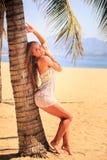 blondes Mädchen in der Spitzenahaufnahme lehnt sich mit Rückseite auf Palme auf Strand Lizenzfreie Stockfotos