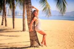 blondes Mädchen in der Spitzenahaufnahme lehnt sich zurück auf Palmenlächeln auf Strand Lizenzfreie Stockfotos