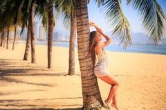 blondes Mädchen in der Spitzenahaufnahme lehnt sich zurück auf Palmenlächeln auf Strand Lizenzfreie Stockbilder