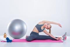 Blondes Mädchen in der Sportkleidung tut Übungen auf Eignung Matte auf grauem Hintergrund ausdehnen Lizenzfreie Stockfotos