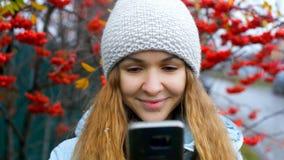 Blondes Mädchen in der Strickmütze surft Internet am roten Ebereschenbaum stock footage