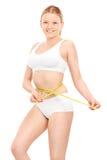 Blondes Mädchen in der Unterwäsche, die ihre Taille misst Stockbilder