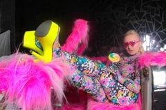 Blondes Mädchen der Vereinpartei in saurem Animeart Spandex catsuit mit Spiegelauto mit dem Rosapelz bereit zum verrückten Clubbi stockfotos