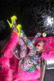 Blondes Mädchen der Vereinpartei in saurem Animeart Spandex catsuit mit Spiegelauto mit dem Rosapelz bereit zum verrückten Clubbi stockfotografie