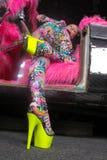 Blondes Mädchen der Vereinpartei in saurem Animeart Spandex catsuit mit Spiegelauto mit dem Rosapelz bereit zum verrückten Clubbi stockfoto