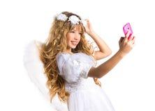 Blondes Mädchen des Engels, das Bildhandy- und -federflügel nimmt Stockbilder