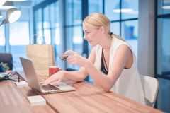 Blondes Mädchen des glücklichen Geschäfts, das eine Kreditkarte auf Einkaufen-onlin verwendet Stockfoto