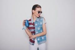 Blondes Mädchen des Hippies in der amerikanischen patriotischen Ausstattung und in der Sonnenbrille, die Getränkedose lokalisiert Lizenzfreie Stockfotografie