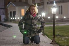 Blondes Mädchen des Nachtporträts in einem warmen Mantel Stockbild