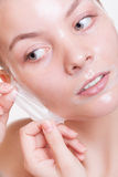 Blondes Mädchen des Porträts in Gesichts ziehen weg Maske ab. Schönheit und Hautpflege. Stockfotografie