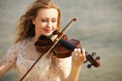 Blondes Mädchen des Porträts mit einer Violine im Freien Stockfoto