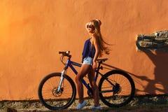 Blondes Mädchen des recht jungen Hippies, das mit Sportfahrrad aufwirft Lizenzfreies Stockfoto