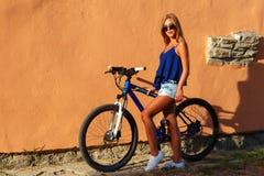 Blondes Mädchen des recht jungen Hippies, das mit Sportfahrrad aufwirft Lizenzfreie Stockfotografie