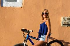 Blondes Mädchen des recht jungen Hippies, das mit Sportfahrrad aufwirft Stockbilder