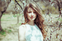 Blondes Mädchen des schönen Frühlinges in blühendem Baum Stockfotografie