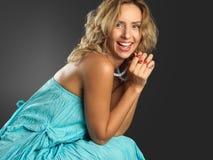 Blondes Mädchen des Toothy Lächelns im grünen Kleid Lizenzfreie Stockfotografie