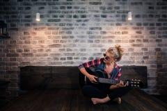 Blondes Mädchen des Zaubers in der verursachenden Kleidung, die Musik auf Gitarre spielt Lizenzfreie Stockfotos
