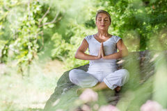 Blondes Mädchen des Zens 20s, das auf einem großen Stein meditiert Stockfoto