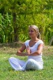 Blondes Mädchen des Zens 20s, das, Parkumgebungen sich wiederbelebt Stockfotografie