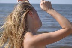 Blondes Mädchen in einem Bikini auf dem Strand Schöne junge Frau in einem bunten Bikini auf Seehintergrund Stockbilder