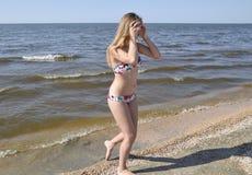 Blondes Mädchen in einem Bikini auf dem Strand Schöne junge Frau in einem bunten Bikini auf Seehintergrund Stockfotos