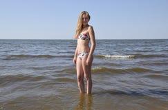 Blondes Mädchen in einem Bikini auf dem Strand Schöne junge Frau in einem bunten Bikini auf Seehintergrund Lizenzfreies Stockbild