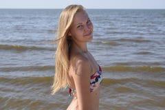 Blondes Mädchen in einem Bikini auf dem Strand Schöne junge Frau in einem bunten Bikini auf Seehintergrund Stockbild