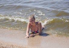 Blondes Mädchen in einem Bikini, der auf dem Strand liegt und die Wellen spritzen auf ihm Schöne junge Frau in einem bunten Bikin Stockfotografie