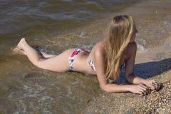 Blondes Mädchen in einem Bikini, der auf dem Strand liegt und die Wellen spritzen auf ihm Schöne junge Frau in einem bunten Bikin Stockfotos
