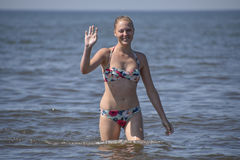Blondes Mädchen in einem Bikini, der aus das Meerwasser herauskommt Schöne junge Frau in einem bunten Bikini auf Seehintergrund Lizenzfreies Stockbild