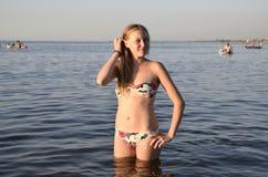 Blondes Mädchen in einem Bikini, der im Meerwasser steht Schöne junge Frau in einem bunten Bikini auf Seehintergrund Lizenzfreie Stockfotos