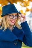 Blondes Mädchen in einem blauen Hut richtet Gläser gerade Stockfotografie