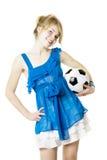 Blondes Mädchen in einem blauen Kleid mit Fußballkugel Stockfoto