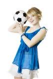 Blondes Mädchen in einem blauen Kleid mit Fußballkugel Lizenzfreie Stockfotos