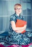 Blondes Mädchen in einem Glas, das auf einem Fenster sitzt und rotes Kissen hält Stockfotos