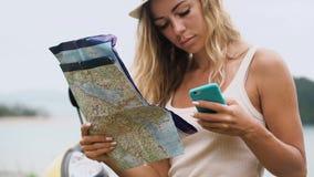 Blondes Mädchen in einem Hut, sitzt auf einem Fahrrad und betrachtet das Telefon und eine Karte, betrachtet den Weg in Asien stock footage