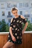 Blondes Mädchen in einem Kleid mit Blumen auf dem Hintergrund des Hauses Lizenzfreie Stockfotos